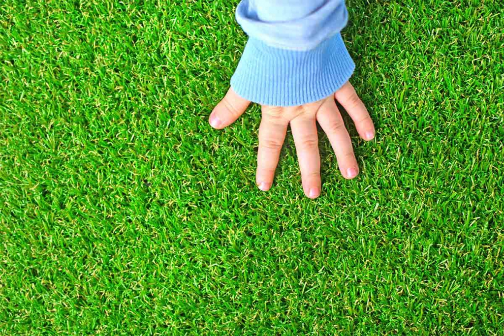 child touching synthetic grass or turf