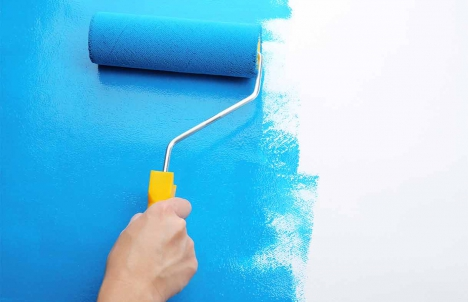 paint roller applying blue paint on a wall