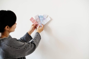 woman comparing paint samples in front of wall