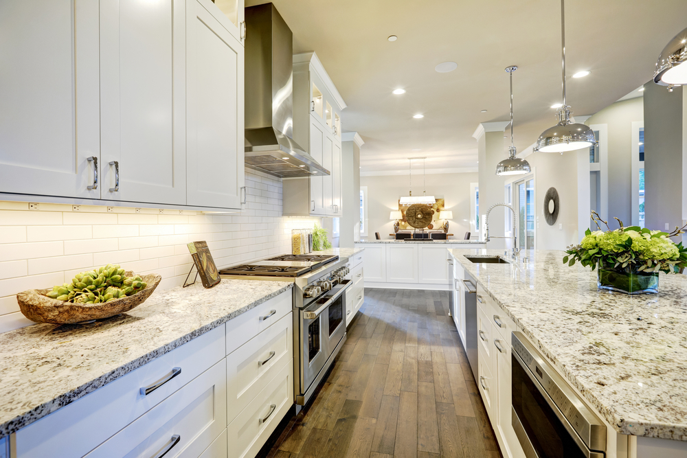 galley-style kitchen with white cabinets wood floor and gray granite countertops