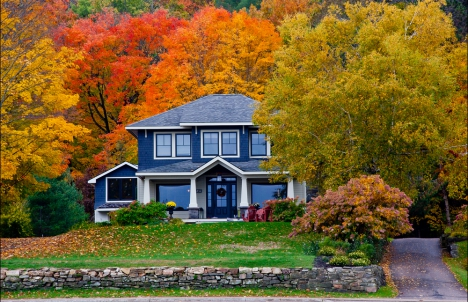 Traditional home with blue siding surrounded by autumn foliage