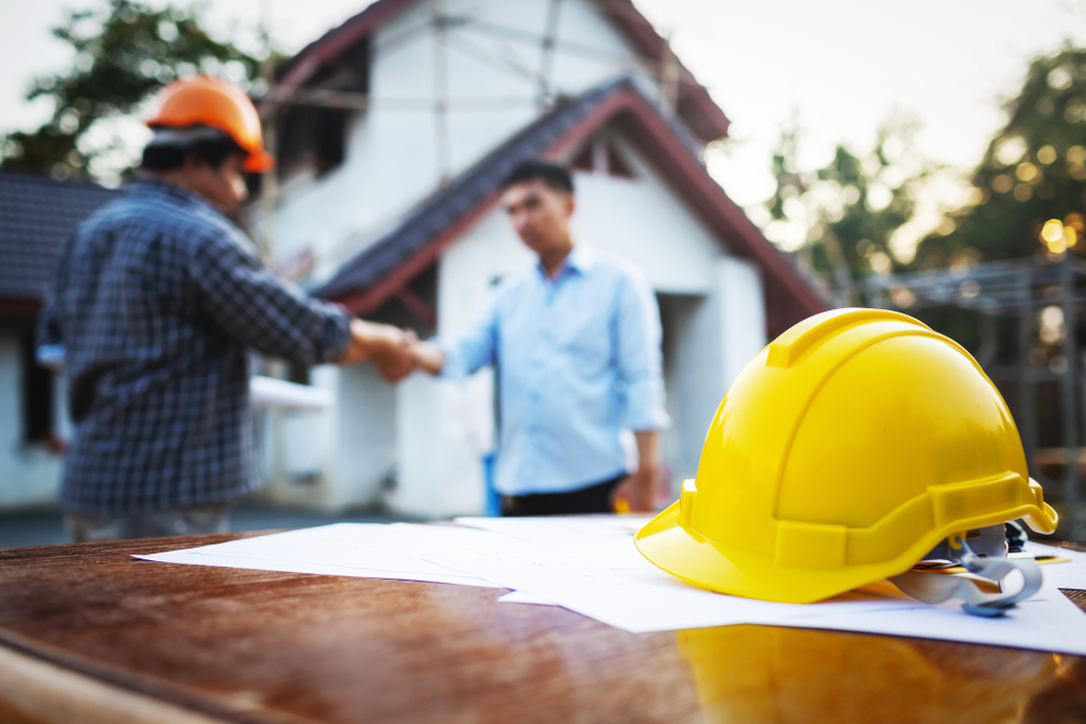 Contractor and homeowner shaking hands with hard hat and contract in foreground