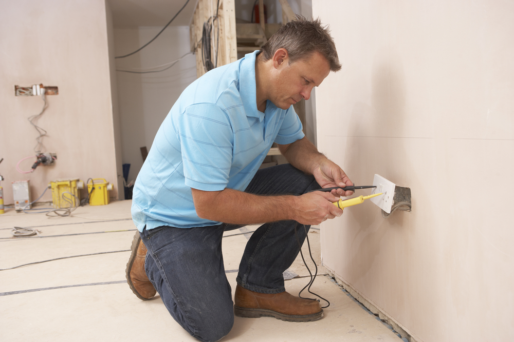 Electrician installing wall outlet