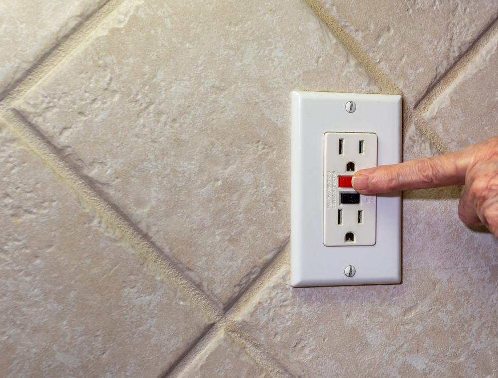 Hand resetting a tripped GFCI outlet