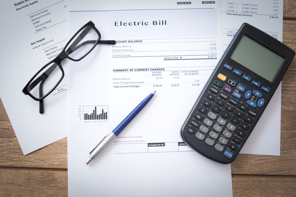Electric bill on table with calculator, eyeglasses, and pen