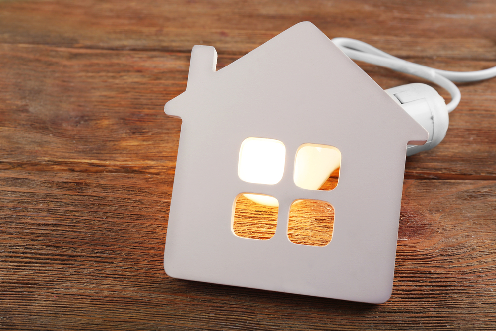 Home energy concept with light bulb illuminating a plastic house on wood background