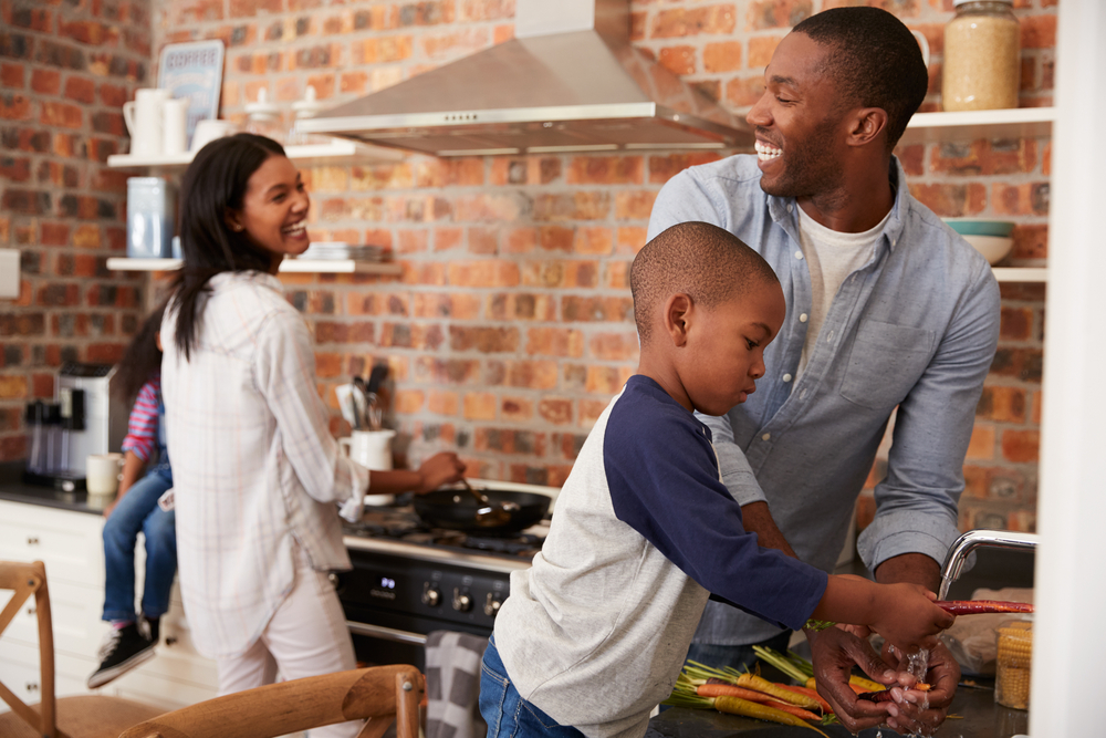 children helping parents prepare dinner in kitchen