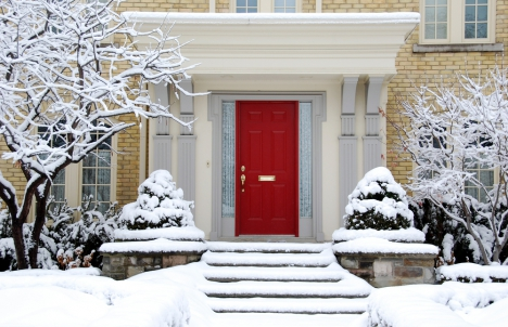 Pale brick home with red front door covered in snow