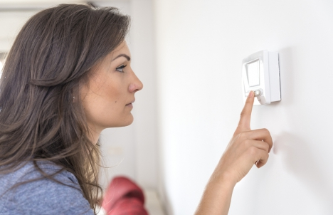 woman adjusting digital thermostat at home