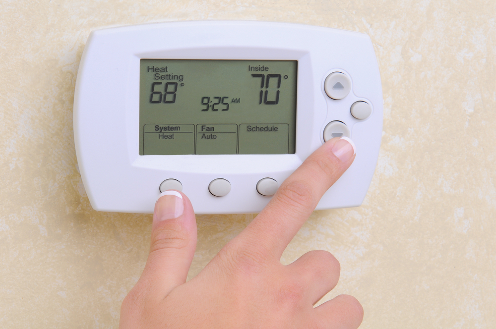 Close-up image of a woman's hand adjusting a digital thermostat