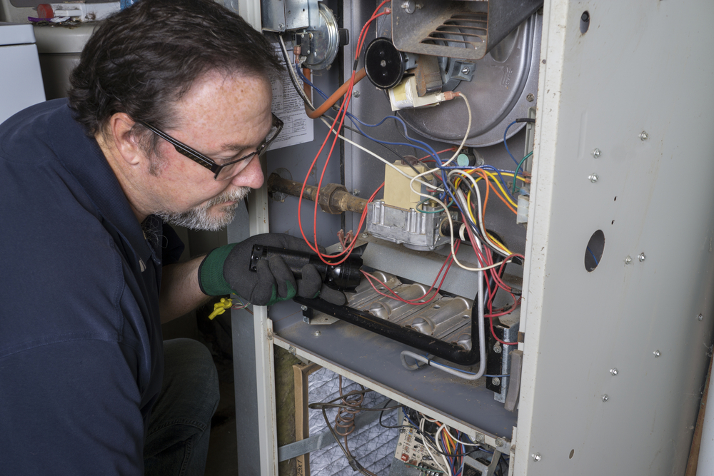 alt tag: An HVAC professional inspecting a gas furnace