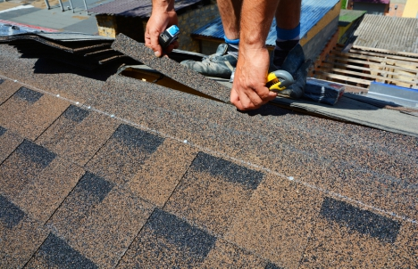 Close-up of hands installing roof shingles