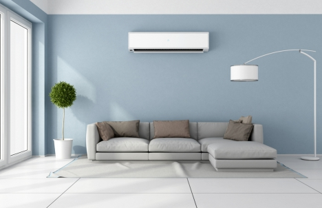 Modern living room with A/C unit above gray couch