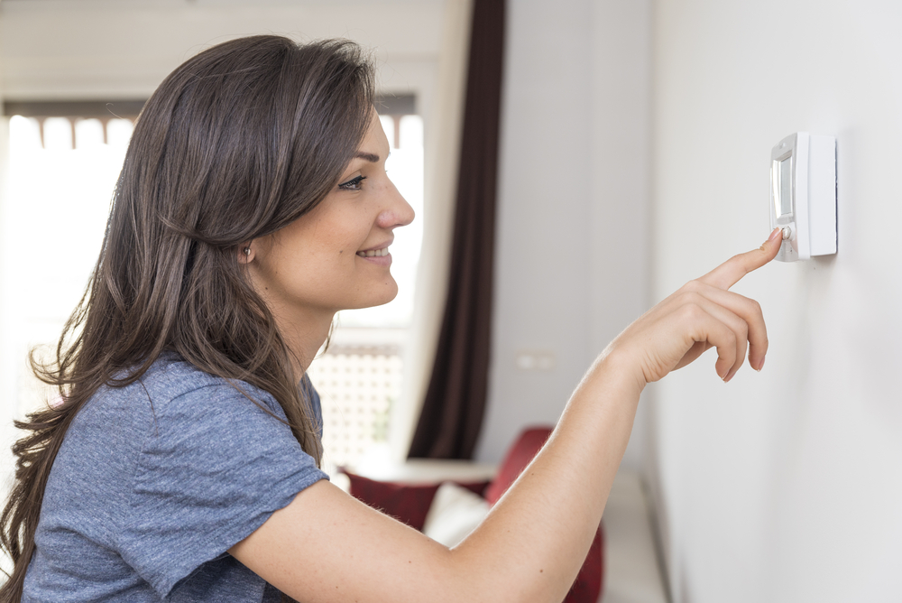 woman adjusting the thermostat