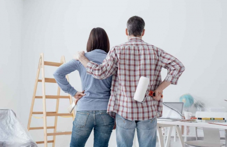 couple looking at wall with paint brushes