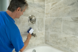 Man cleaning grout in bathroom tiles