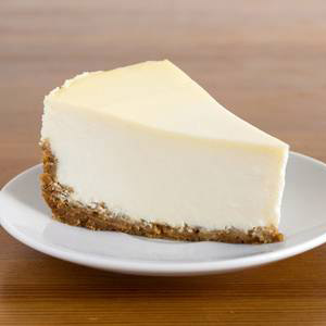 50840915 slice of plain new york cheesecake on white plate on wooden background