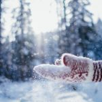 Person playing in the snow with red mittens on
