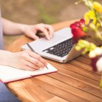 Freelancer working in the garden. Writing, surfing in the internet. Young girl. Relax and joy.