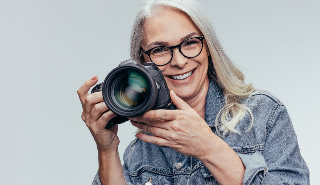 Senior woman photographer holding a DSLR camera. Smiling female photographer taking pictures with professional camera.