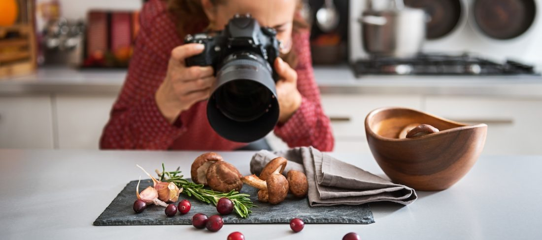 A woman food photographer in the background leans down to take a close-up, in a modern kitchen, of autumn fruits and vegetables - mushrooms, garlic, rosemary, and cranberries.