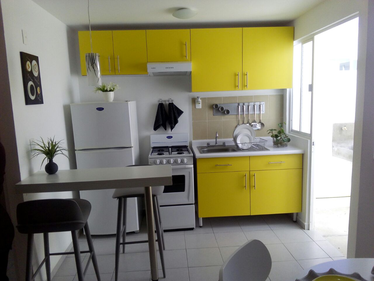 Cocina integral amarilla de casa en venta en VARADERA RESIDENCIAL Queretaro