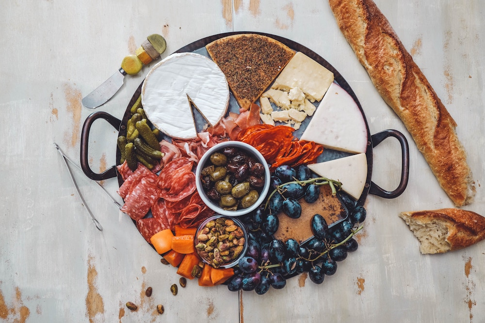 overhead photo of cheese and charcutterie plate with grapes