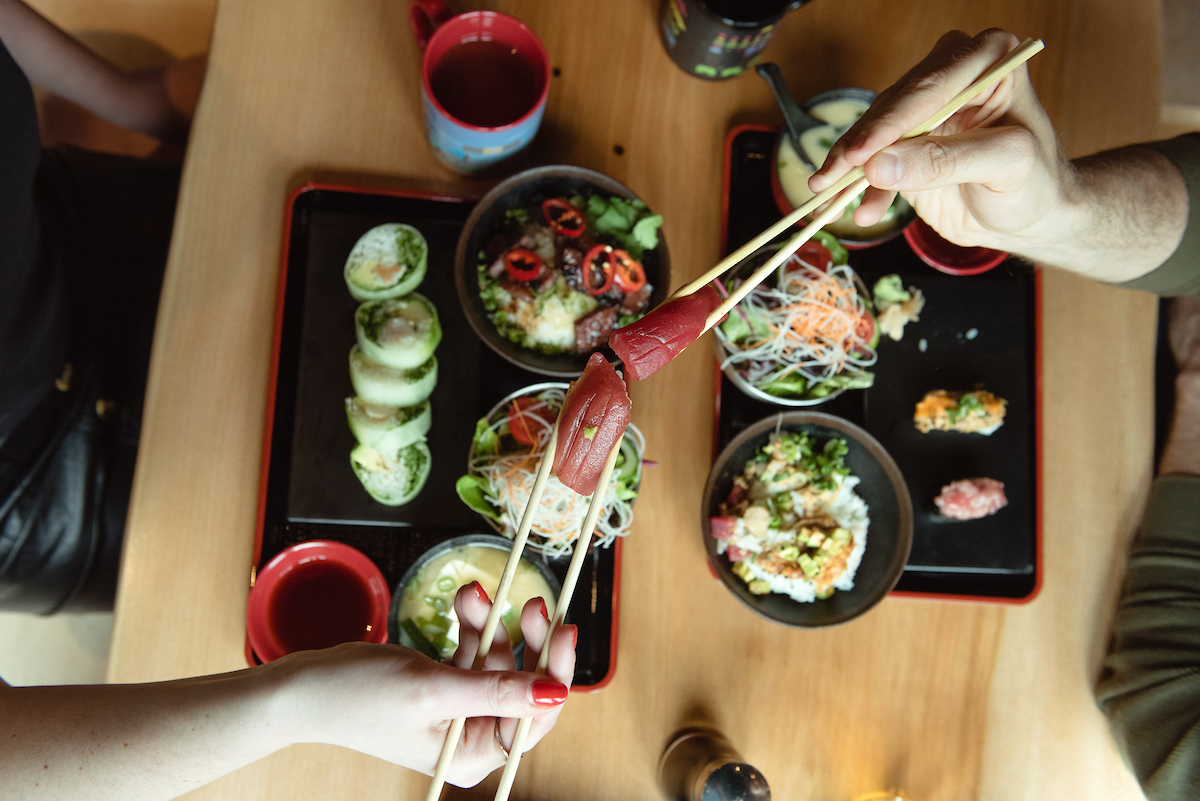 overhead shot of a table of sushi with two people cheersing with sushi