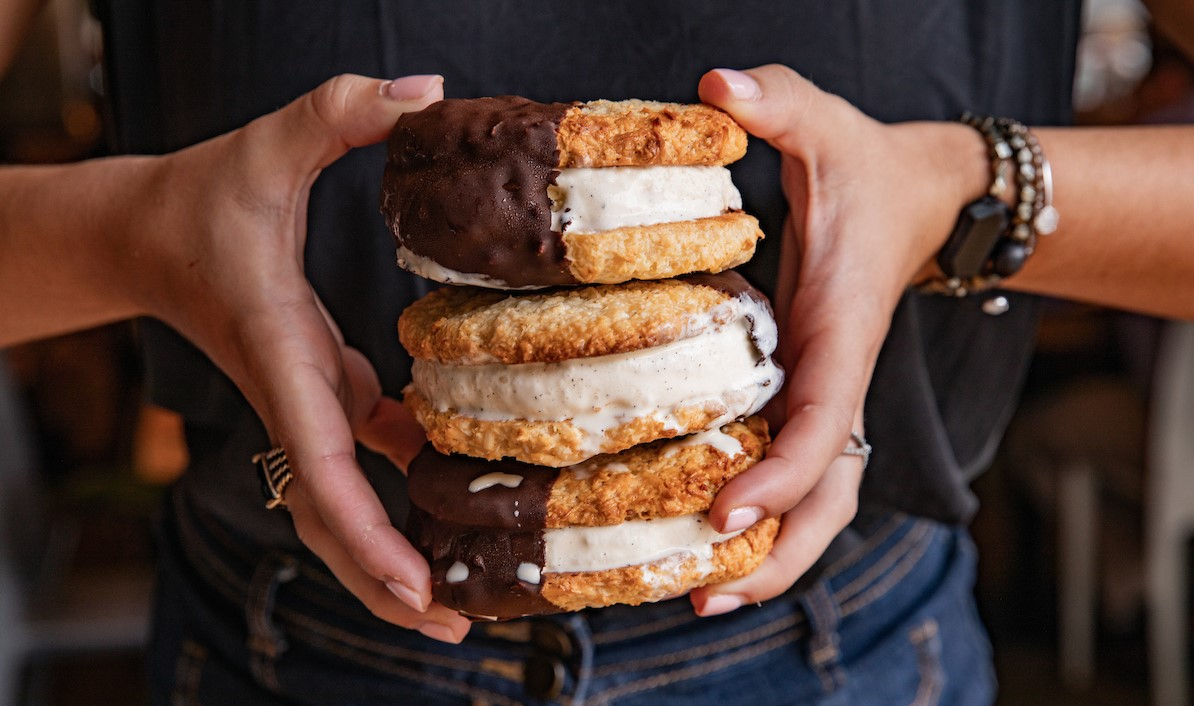 a person holding a stack of three ice cream sandwiches