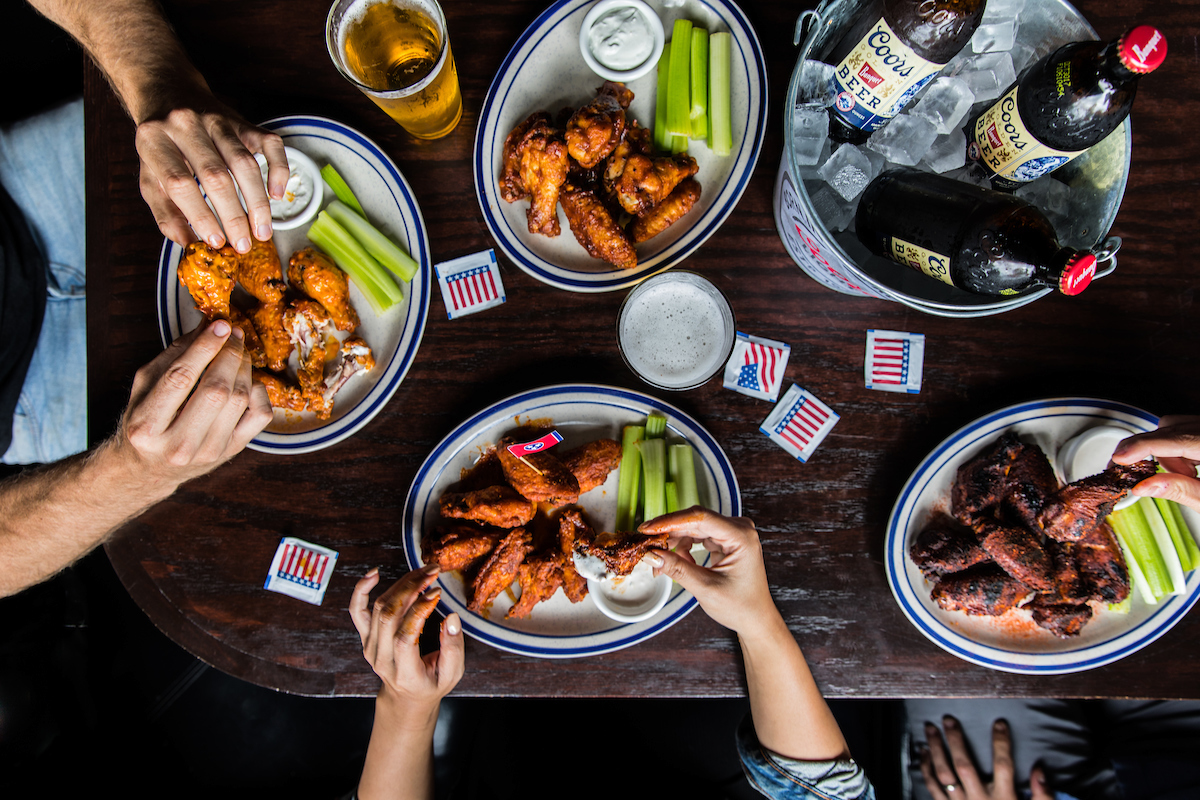 overheadshot of people eating wings with a bucket of beer on the table