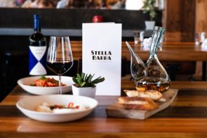 Table spread with wine carafes, salads, vegetables, pizza and authentic Italian pasta at Stella Barra Pizzeria and Wine Bar Santa Monica.