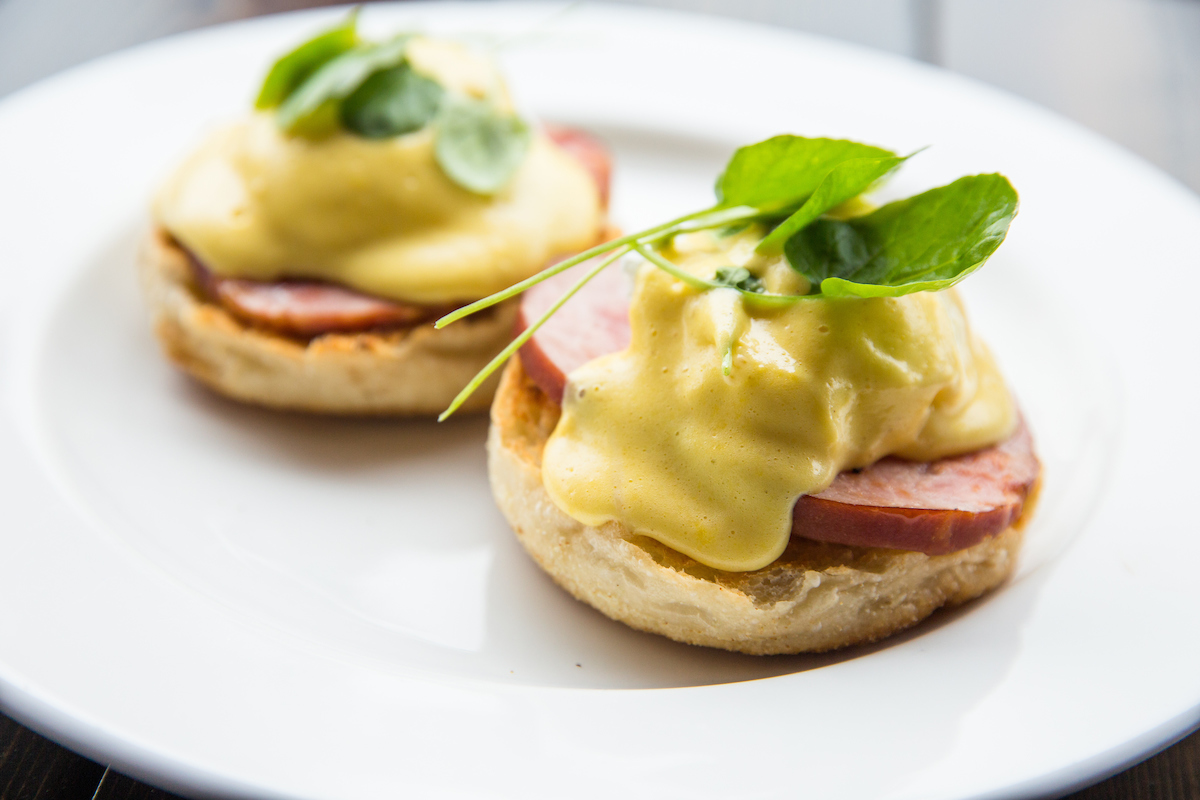 Eggs benedict with ham on an english muffin with sauce and green herbs on top