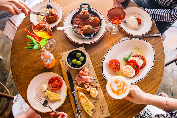 il Porcellino's table of food with people eating it