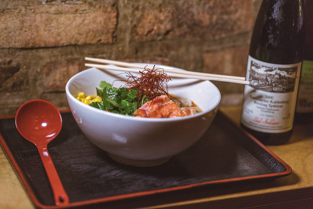 close up of ramen next to a bottle of riesling