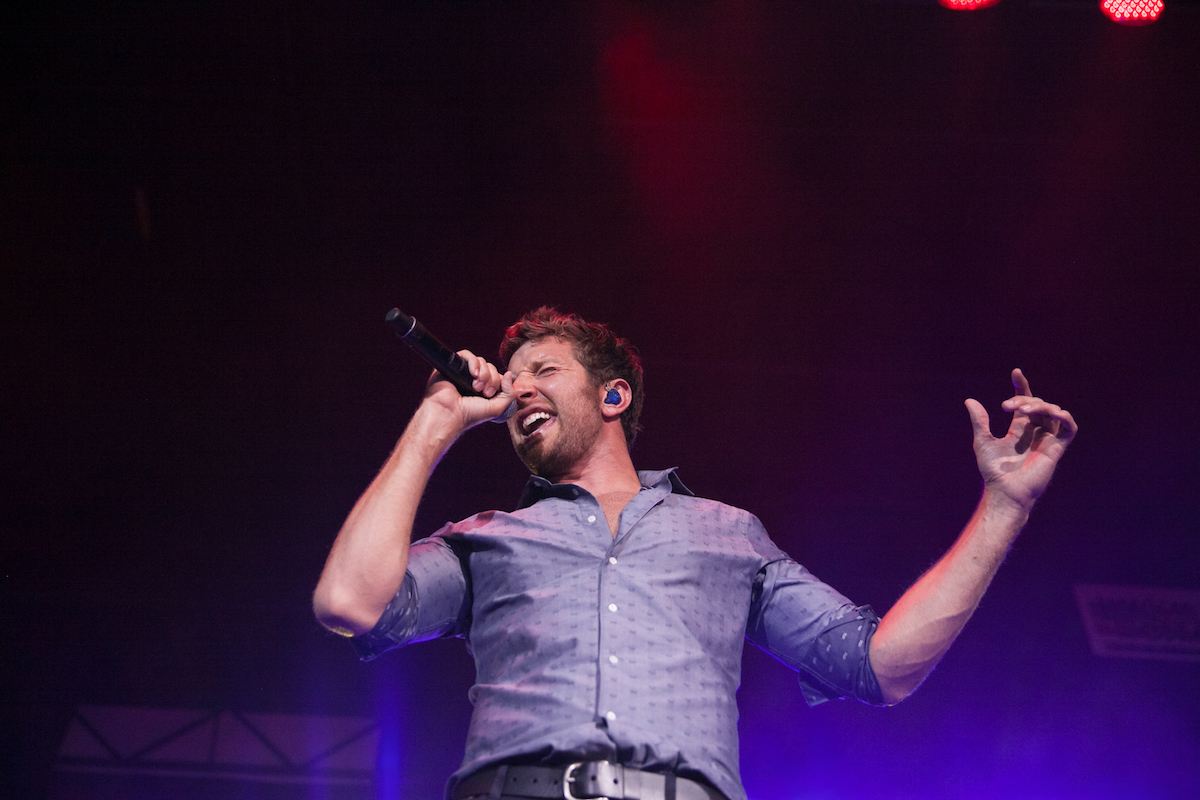 man singing into a mic wearing a purple button down