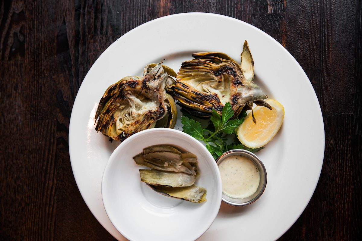 two artichoke halves griled with lemon and aioli, with a bowl of eaten leaves