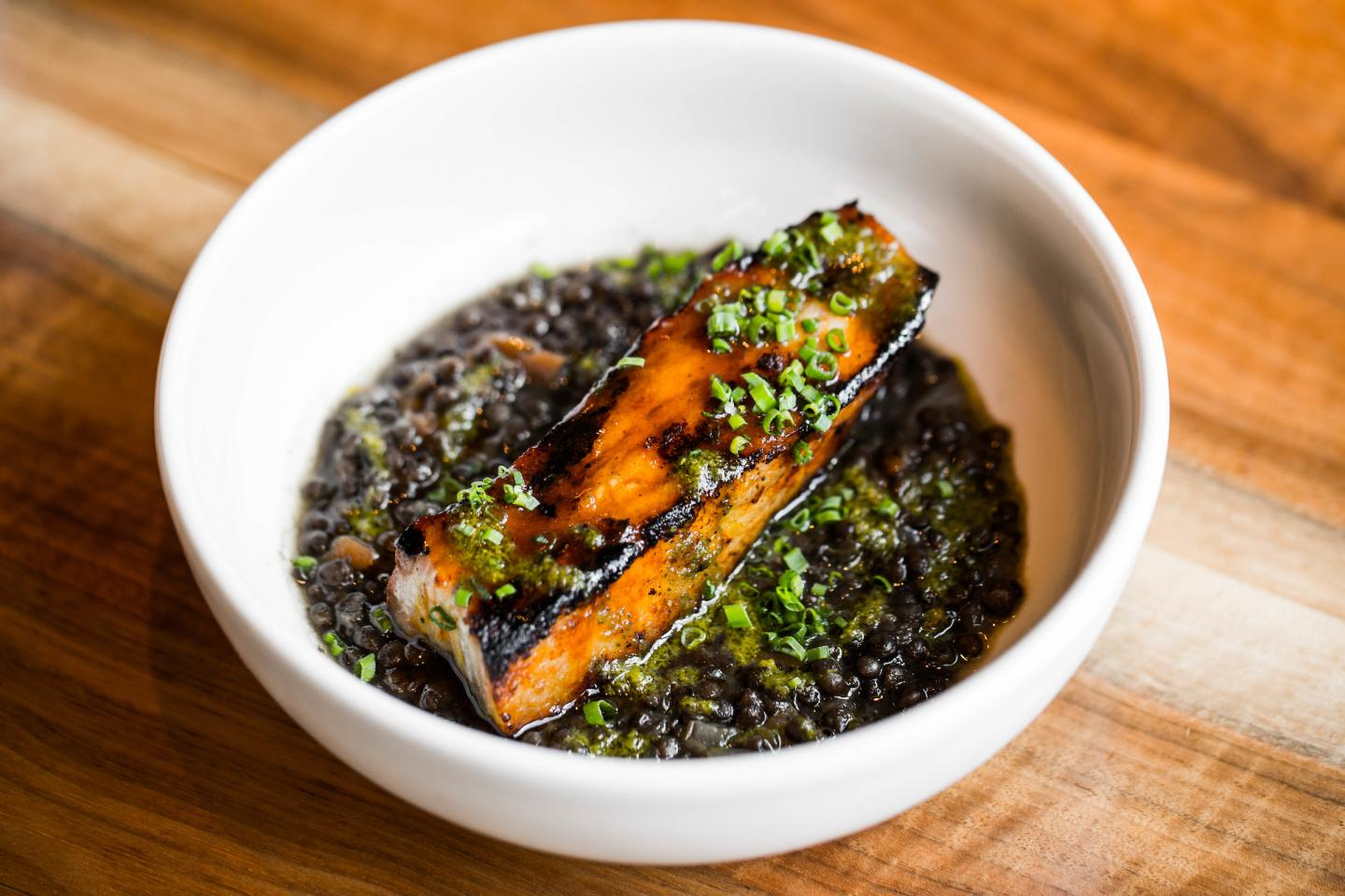 ema's grilled pork belly atop a bed of lentils in a white bowl