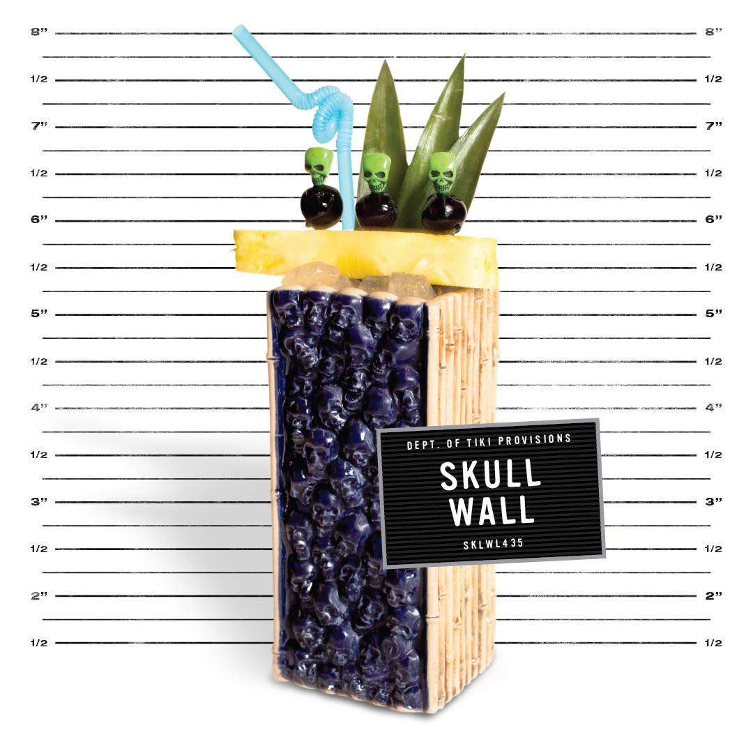 skull wall mug from three dots and a dash with a pineapple studded with brandied cherries, a blue straw and three pineapple fronts, in front of a police mug shot