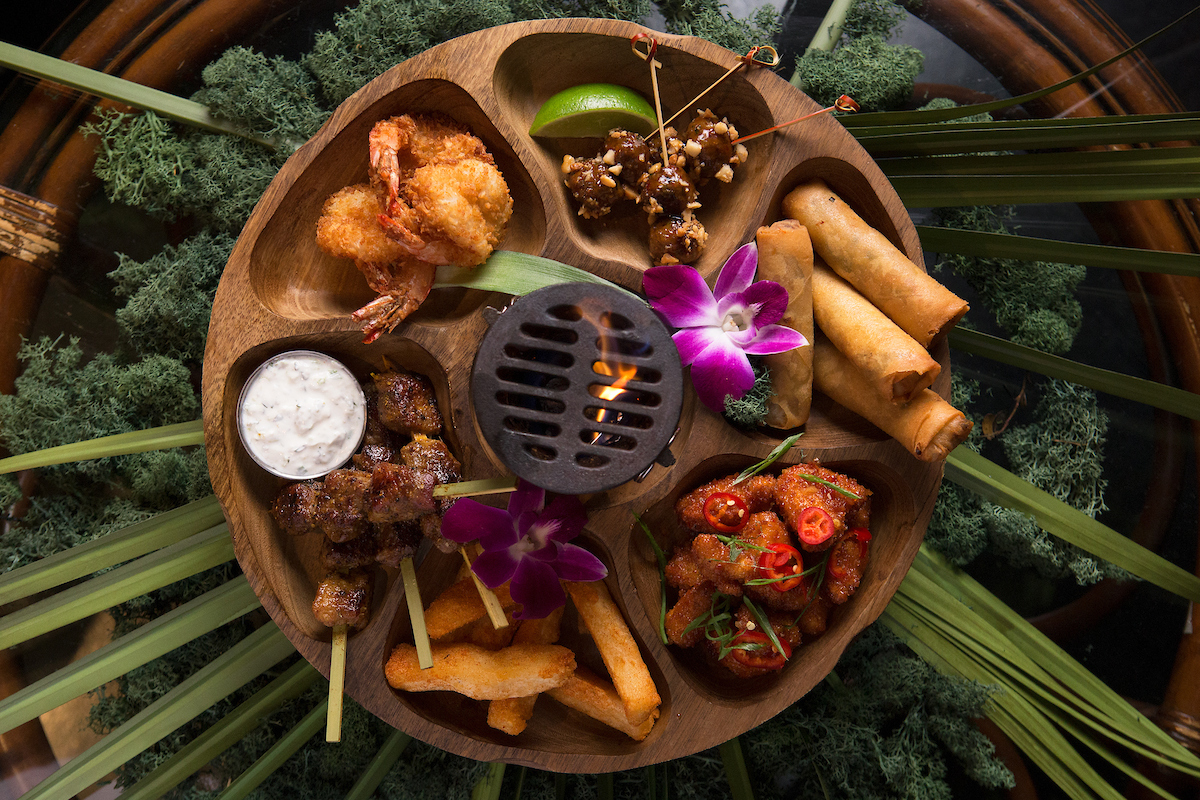 overhead shot of three dots' pu pu platter with egg rols, fried shrimp, pork skewers and more!