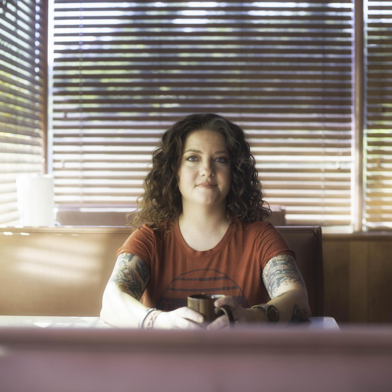 ashley mcbryde wearing an orange t shirt sitting in a diner