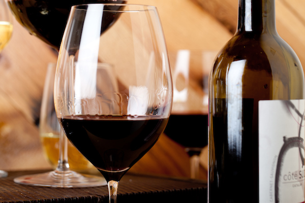 close up image of a red wine glass with a bottle and 2 more glasses in the background