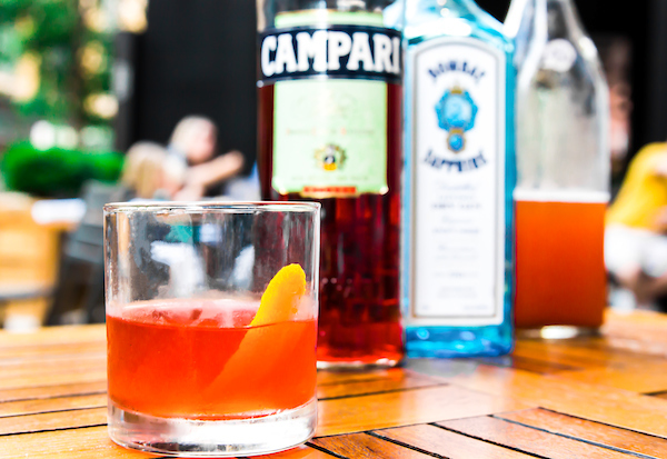 negroni on a table in front of a bottle of campari