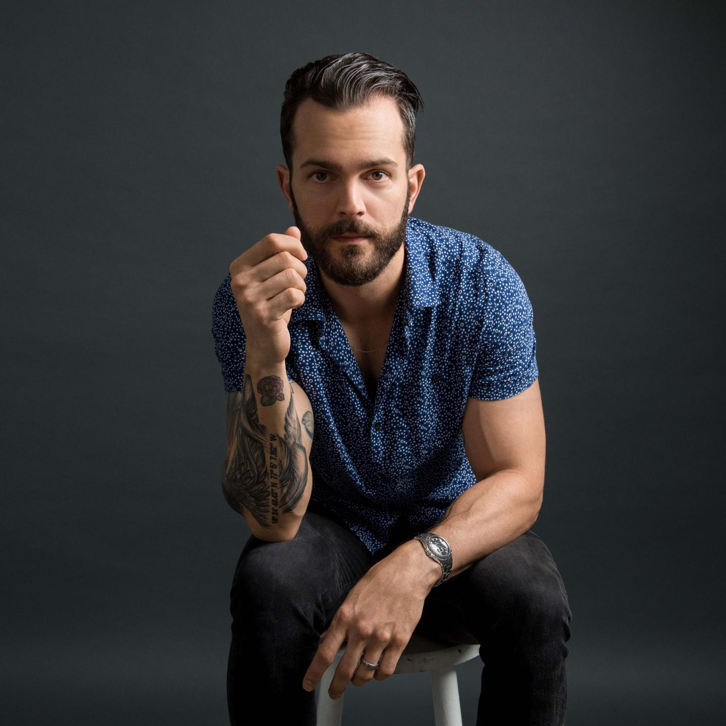 ryan kinder sitting on a stool against a gray background