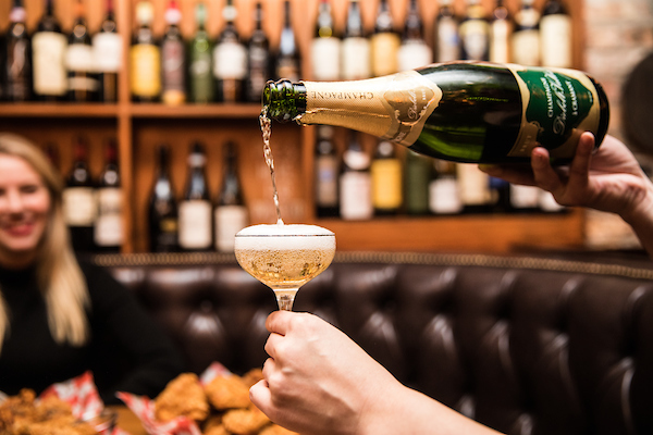 someone pouring champagne into a coupe at il porcellino