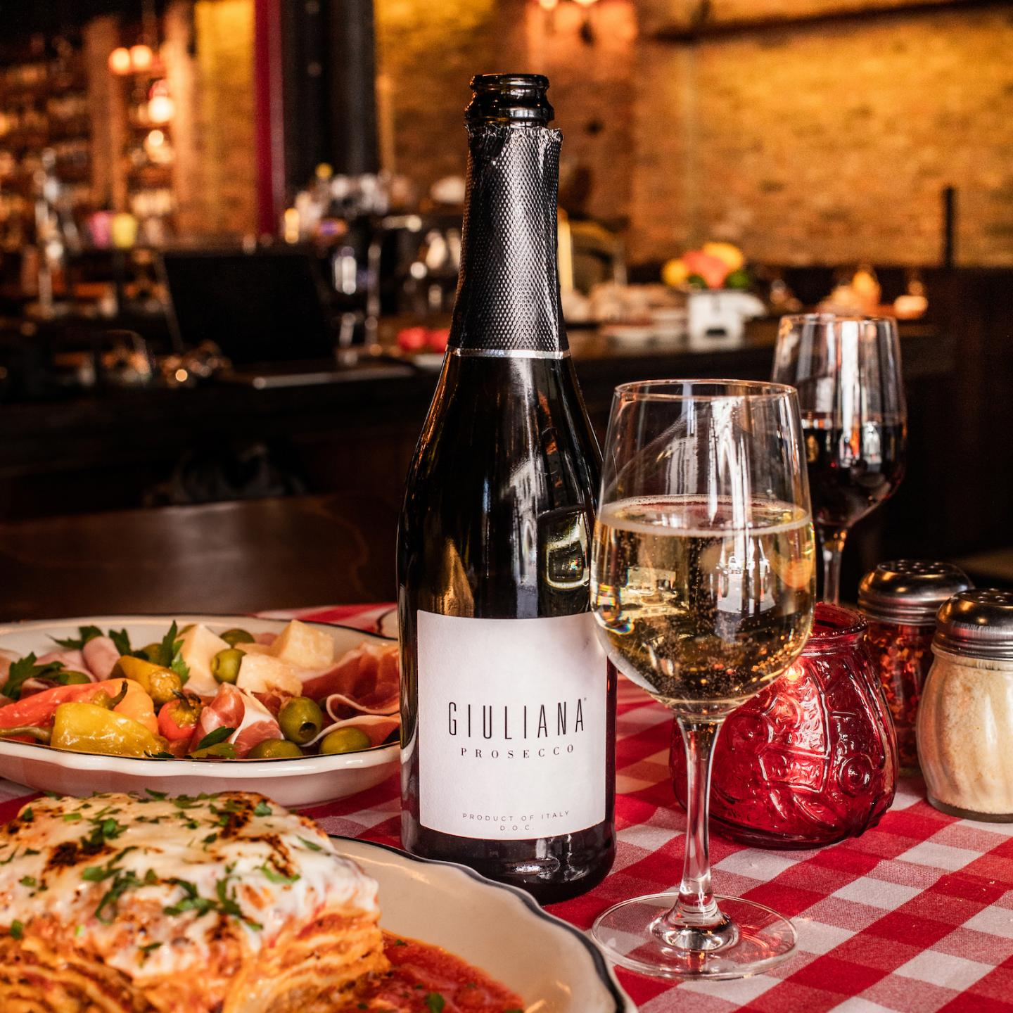 bottle of Giuliana Prosecco and glass of wine with food on the table at il Porcellino