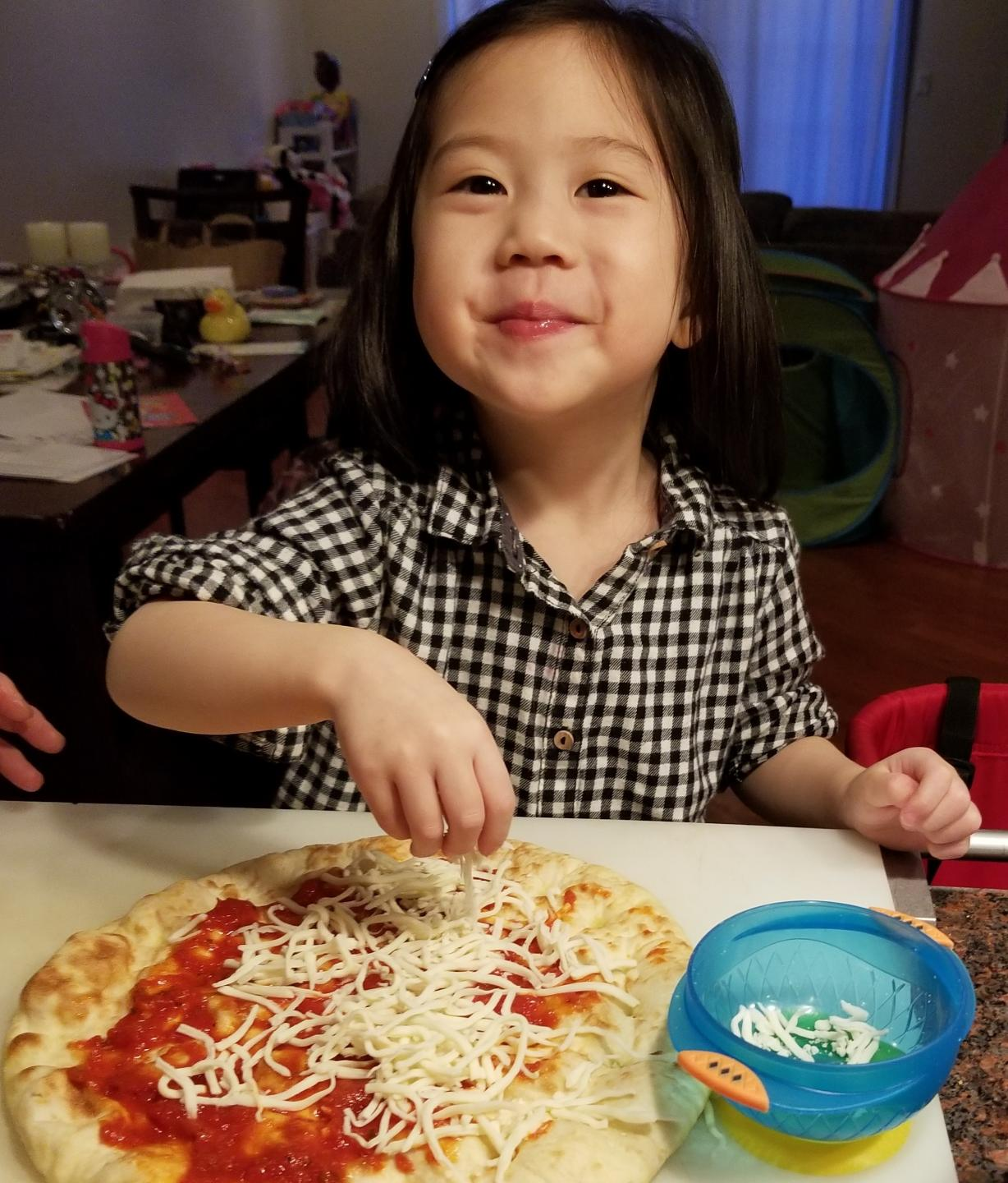 little girl making pizza