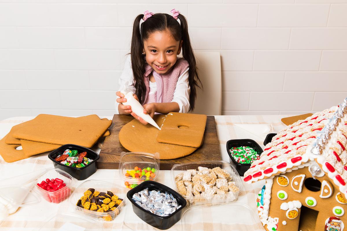 Little girl making a gingerbread house