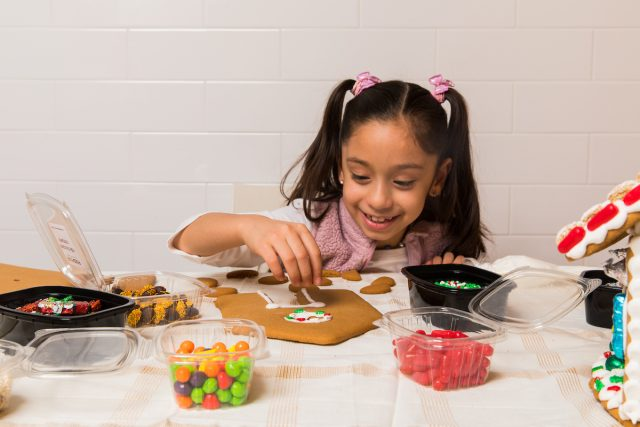 little girl decorating gingerbread house cookie