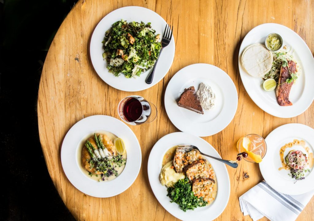 Four entrees and a slice of pie on a table at Beatrix