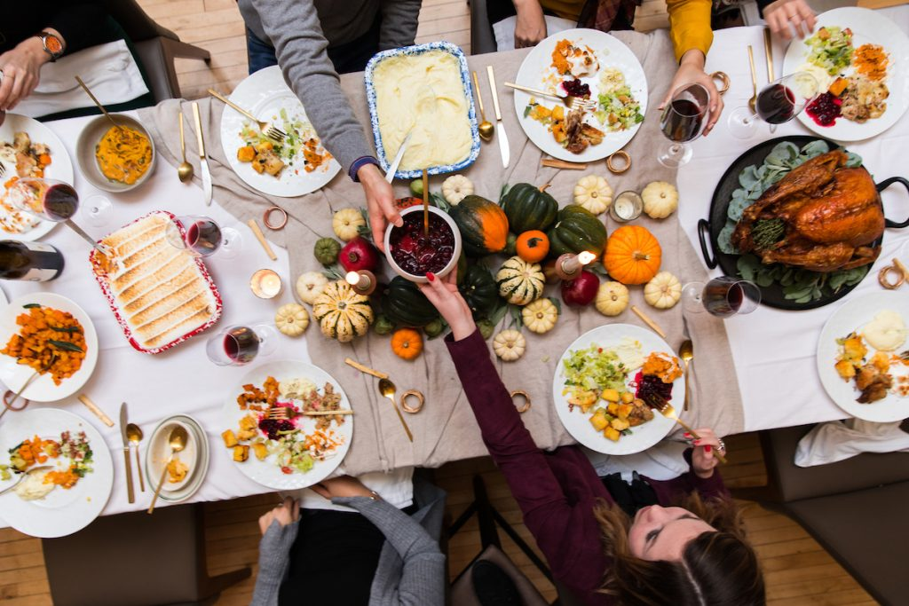 A Thanksgiving dinner table filled with food and surrounded by people